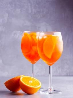 Aperol spritz коктейль на сером фоне. два стакана aperol spritz с апельсиновой нарезкой. летний итальянский коктейль в бокале.