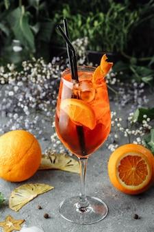 Коктейль aperol spritz на сером бетонном столе. стакан аперола с дольками апельсина. летний коктейль в стакане.