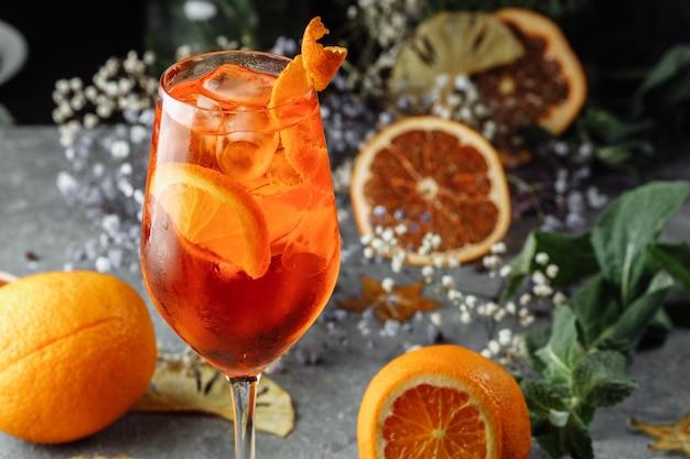 灰色のコンクリートのテーブルでaperolスプリッツカクテル。オレンジスライスのaperol spritzのガラス。グラスに夏のカクテル。