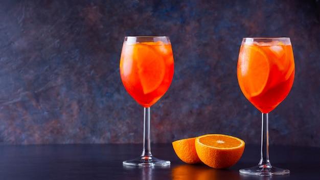 Aperol спритц коктейль на темном фоне. два стакана aperol spritz с апельсиновой нарезкой. летний коктейль в бокале.