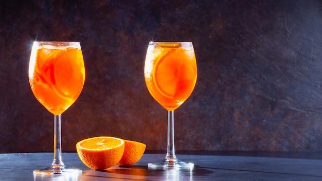 Aperol спритц коктейль на темном фоне. два стакана aperol spritz с апельсиновой нарезкой.
