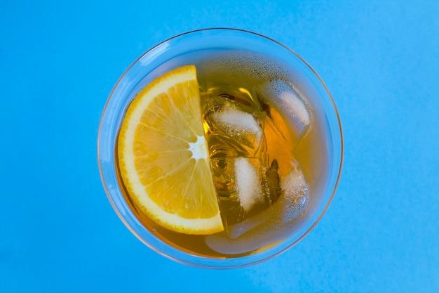 Коктейль aperol spritz или апельсиновый коктейль в бокале мартини в центре синего стола. вид сверху. скопируйте пространство. крупный план.