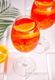 Итальянский коктейль-алкогольный напиток aperol spritz с кубиками льда и апельсинами.