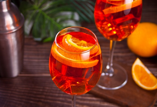 Aperol spritz italian cocktail alcoholic beverage with ice cubes and oranges.