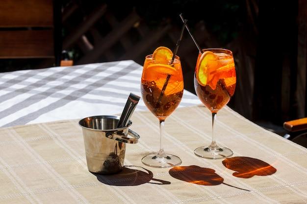 Aperol spritz коктейль стеклянный плед стол листья солнце оранжевый ведро льда тень солнечный свет