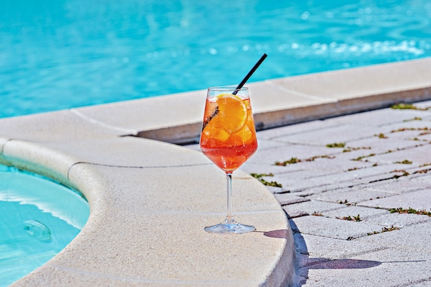 プールサイドの青緑色の水に対して冷たいカクテルaperol spritzのワイングラス