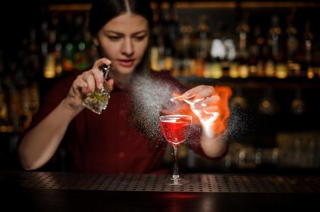 女性のバーテンダーがaperol注射器でカクテルグラスを振りかけ、ピートウイスキーカクテルとバーカウンターでスモーキーなメモを作る