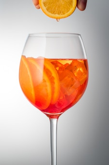 夏の爽やかなかすかなアルコール性のカクテル氷とガラスのガラスのaperolスプライト