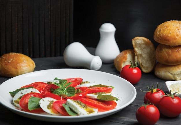 Apetizer salad with mozarella and tomato rolls