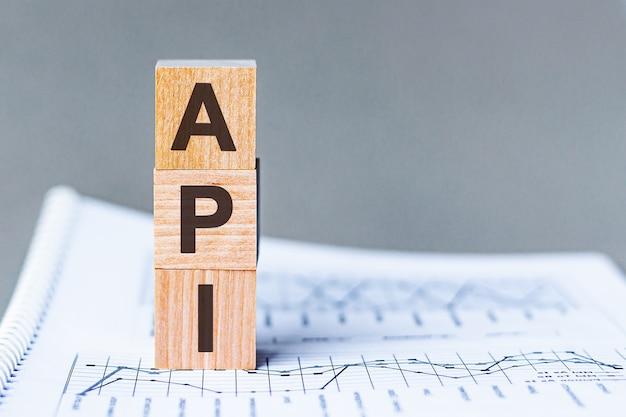 数字の列の表面にある木製の立方体のapiアプリケーションプログラミングインターフェイスの頭字語