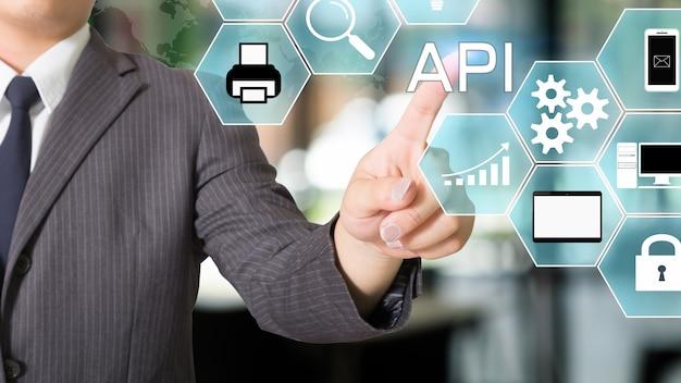 Apiアプリケーションプログラミングインターフェイスの実業家がビジュアルアイコンを指しています。