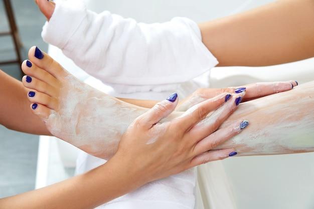 Aplying nourishing moisturizer mask woman legs