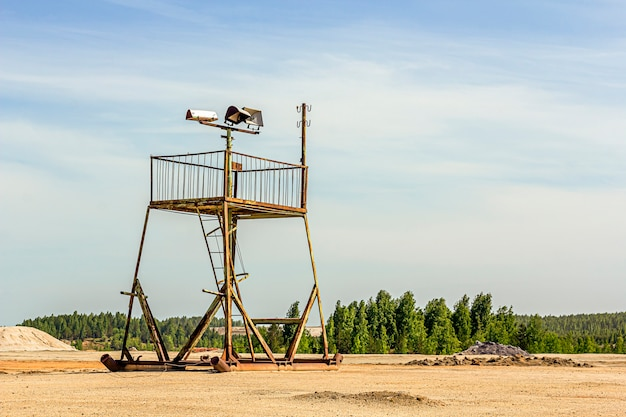 Apocalyptic landscape. abandoned watch tower with rusted iron framework among on cracked and scorched land. solidified white earth surface. a planet without people. global warming concept.