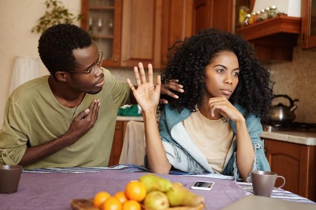 狂牛病の女性を忠実に説得しようとして胸に手を握っている謝罪的なアフリカ系アメリカ人の男性。不貞の夫の言い訳を無視した黒人女性。愛と人間関係の問題