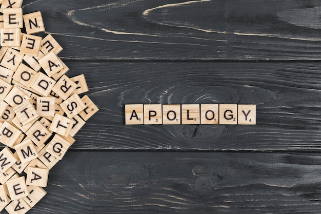 Apology word on wooden background