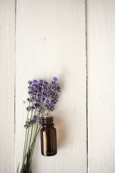 Apothecary lavender oil with a bouquet of flowers. flat lay