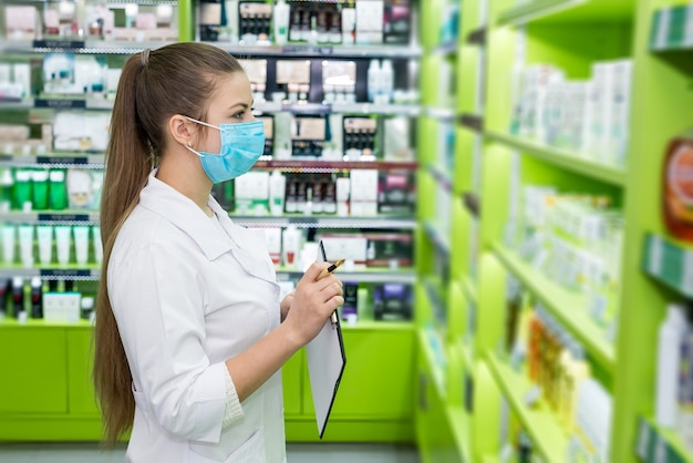 Apothecary looking at medicaments with checklist in drugstore