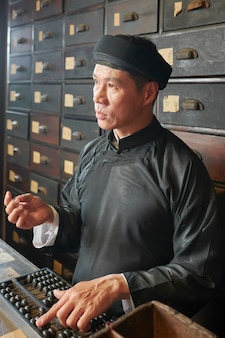 Apothecary worker using abacus