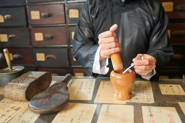Apothecary worker using pestle and mortar