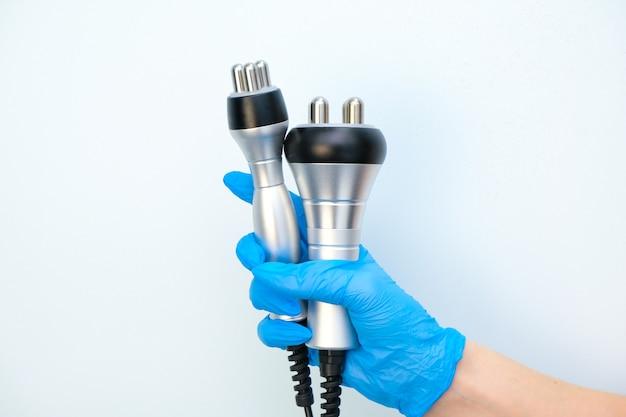 Аппарат массажер ультразвуковой радиочастотный лифтинг в руке косметолога в перчатке