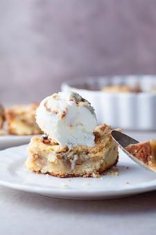 白いプラットの上にアイスクリームを添えたアペクランブルパイのクローズアップ