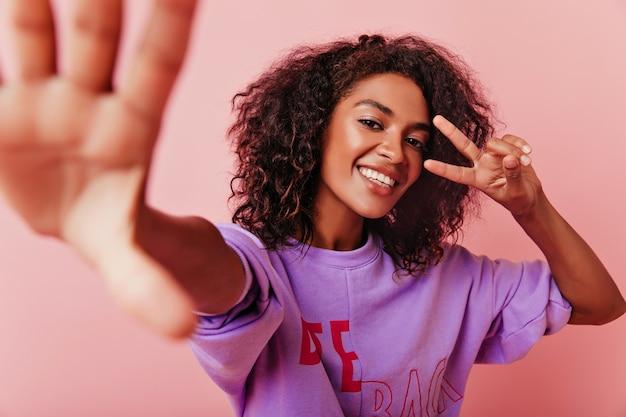Attraente donna africana che fa selfie con segno di pace. ritratto dell'interno della ragazza che ride emotiva in posa sul rosa.