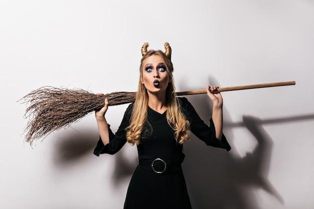 흰 벽에 빗자루를 들고 매력적인 검은 마녀. 할로윈 파티를 즐기는 매력적인 금발의 여자.