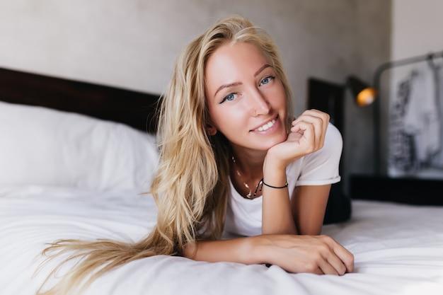 매력적인 파란 눈의 여자가 침대에 누워 카메라를 찾고. 아침을 즐기는 금발 머리와 낭만적 인 세련 된 여자의 실내 샷.