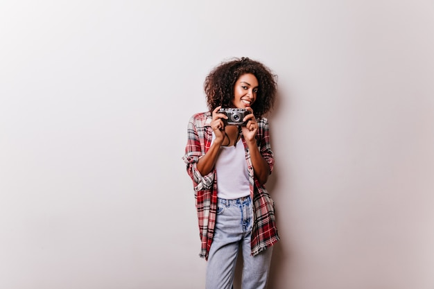 カメラが立っている魅力的な茶色の髪の女性。白で隔離の笑顔のアフリカの女性のショットグラファー。