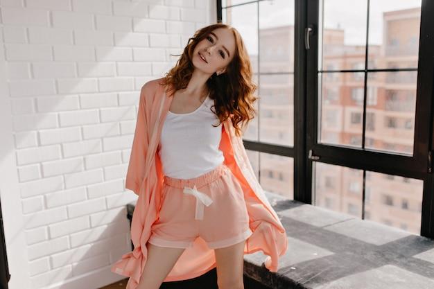 自信を持って立っているパジャマ姿の魅力的な白人の女の子。彼女のフラットでポーズをとる巻き毛の見事な白人女性。
