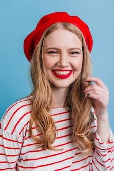 성실한 미소로 포즈를 취하는 프랑스 베레모의 매력적인 소녀. 파란색 벽에 고립 된 매력적인 금발의 여자입니다.