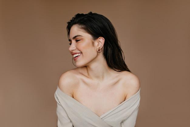 웃 고 매력적인 여자입니다. 검은 머리를 가진 행복한 여성 모델의 실내 사진.