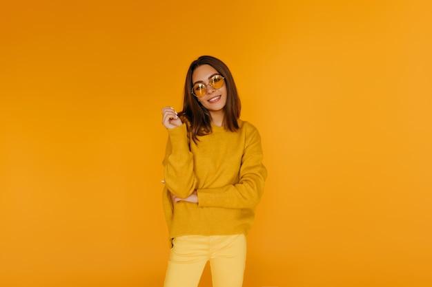Appealing girl in yellow pants smiling. gorgeous caucasian female model in glasses enjoying photoshoot.
