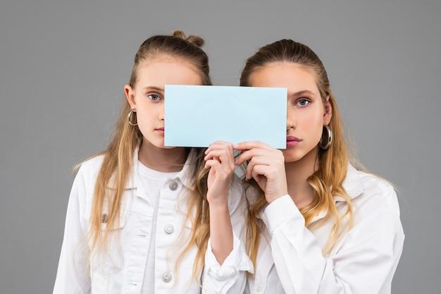 Привлекательные симпатичные похожие девушки в белых нарядах с прозрачной табличкой с именем и закрывающими части лица.