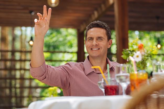 매력적인 남자. 멋진 멋진 레스토랑에 앉아 웨이터를 요청하는 동안 그의 손을 드는 매력적인 남자