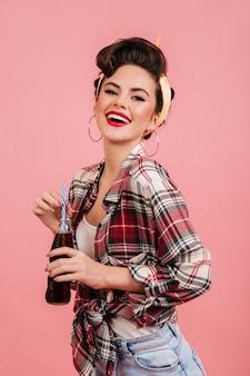カメラに微笑んでいる市松模様のシャツの魅力的なピンナップ女性。ボトルとピンクの背景に分離された魅力的なブルネットの少女のスタジオショット。