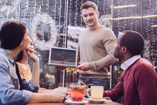 남자가 아래를 내려다 보면서 노트북을 들고있는 동안 카페에서 시간을 보내는 만족스러운 4 명의 동료