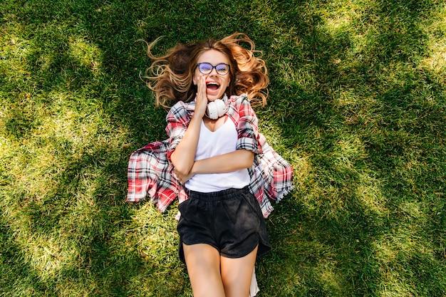 芝生の上に横たわっている魅力的なスリムな女の子。草の上で身も凍るような洗練された金髪の若い女性のオーバーヘッドショット。