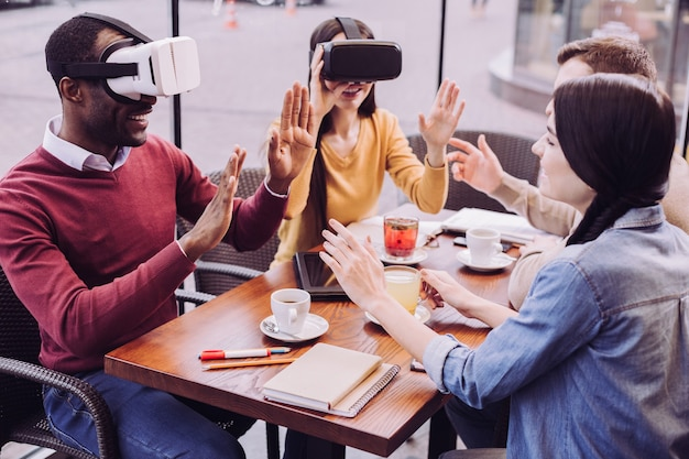 Appealing surprised two friends sitting in cafe while opening mouth and wearing vr headsets