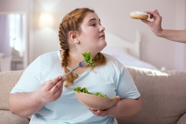 Appealing sweets. plump young woman deciding between salad and donut while sitting on the couch