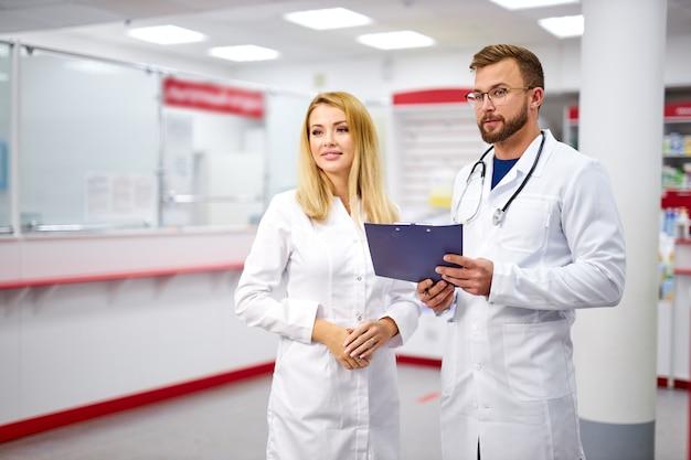 의사 소통하는 매력적인 두 백인 약사