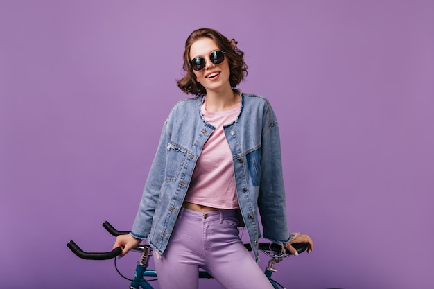 Appealing woman in denim jacket posing with bicycle. indoor shot of confident curly lady isolated.