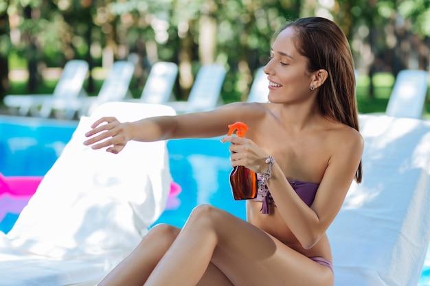 Привлекательная женщина думает о здоровье, используя солнцезащитные средства перед тем, как загорать