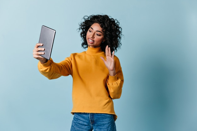 Appealing woman waving hand during video call