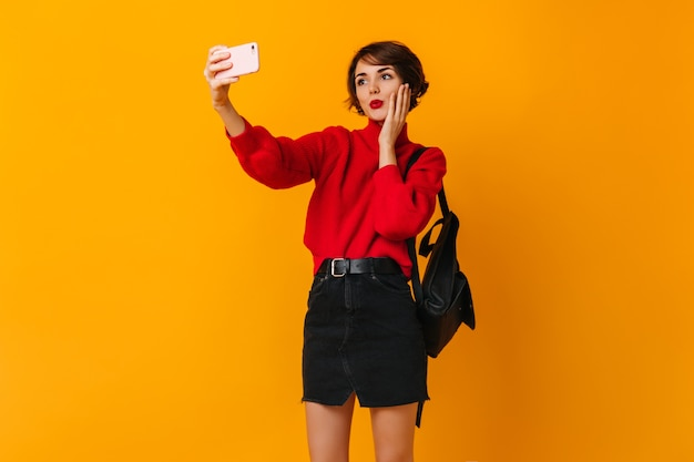 Donna attraente con lo zaino che prende selfie