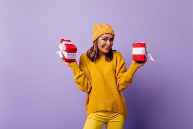 Attraente giovane donna in casual cappello giallo sorridente. ragazza alla moda ben vestita che posa con i regali di compleanno.