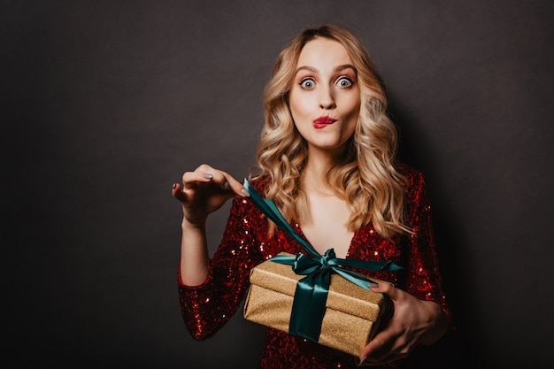 Appealing young woman touching ribbon on new year gift