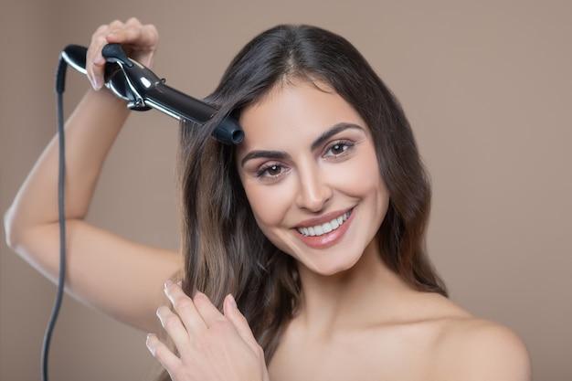 Внешний вид, прическа. счастливая женщина с длинными темными волосами делает волосы щипцами для завивки на бежевом фоне