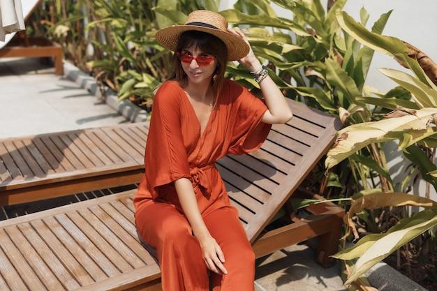 スタイリッシュなオレンジ色の衣装とプールの近くのデッキチェアでゾッとする麦わら帽子でブルネットの女性が表示されます。