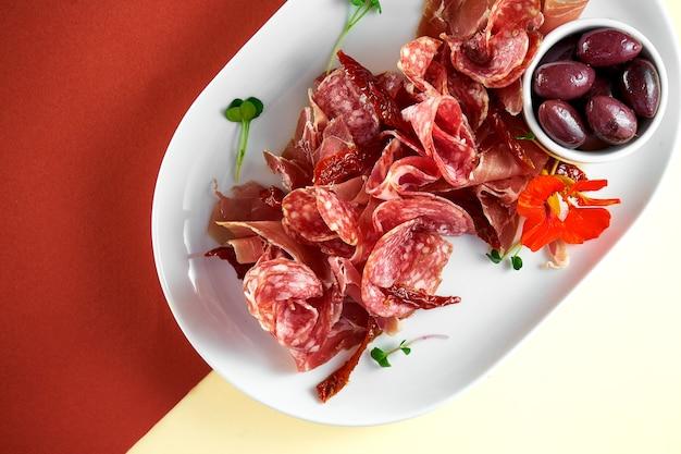 Закуска - мясная тарелка закуски с салями, хамоном и оливками на яркой поверхности